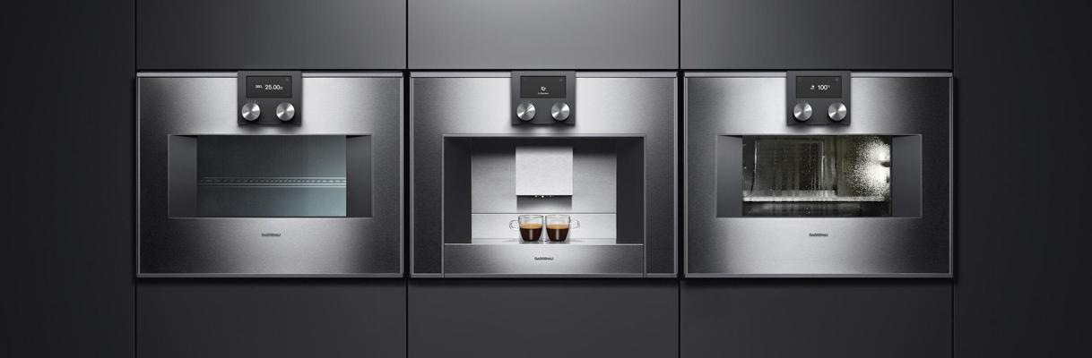Het lijnenspel van een naast elkaar ingebouwde compacte combi-oven, koffiemachine en stoomoven.